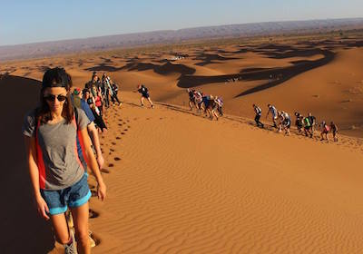 Group of Tourists Trekking across sand dunes in the Sahara Desert, Morocco