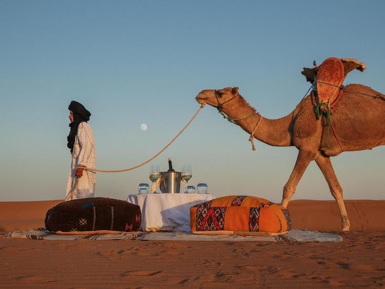 Table for two with Seating Poufs in Moroccan desert and Berber Tribesman with Camel
