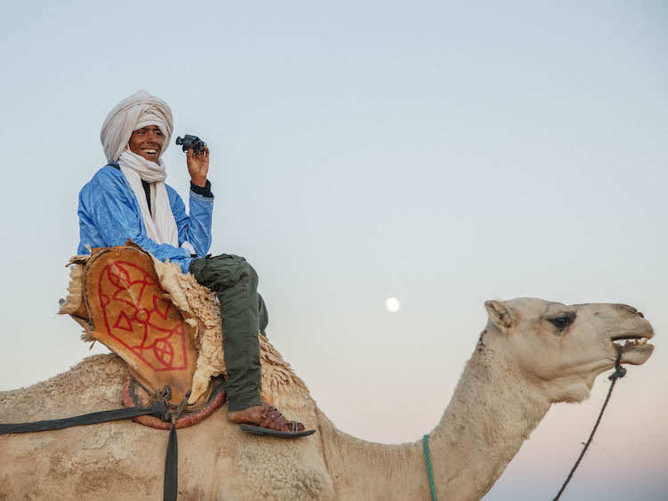 Moroccan Berber Tribesman Smiling sat on Camel holding Video Camera