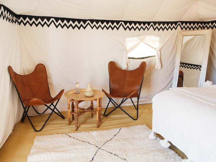 Inside Berber Desert Camp Bedroom, occasional table, and dining chairs