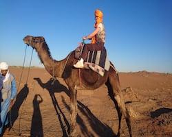 Berber Guide With Tourist on Camel in Sahara Desert Morocco