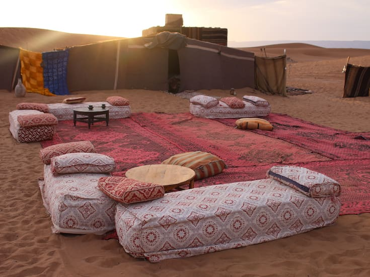 Desert Camp, traditional Persian carpets, sofas, cushions and occasional tables laid out on the sand