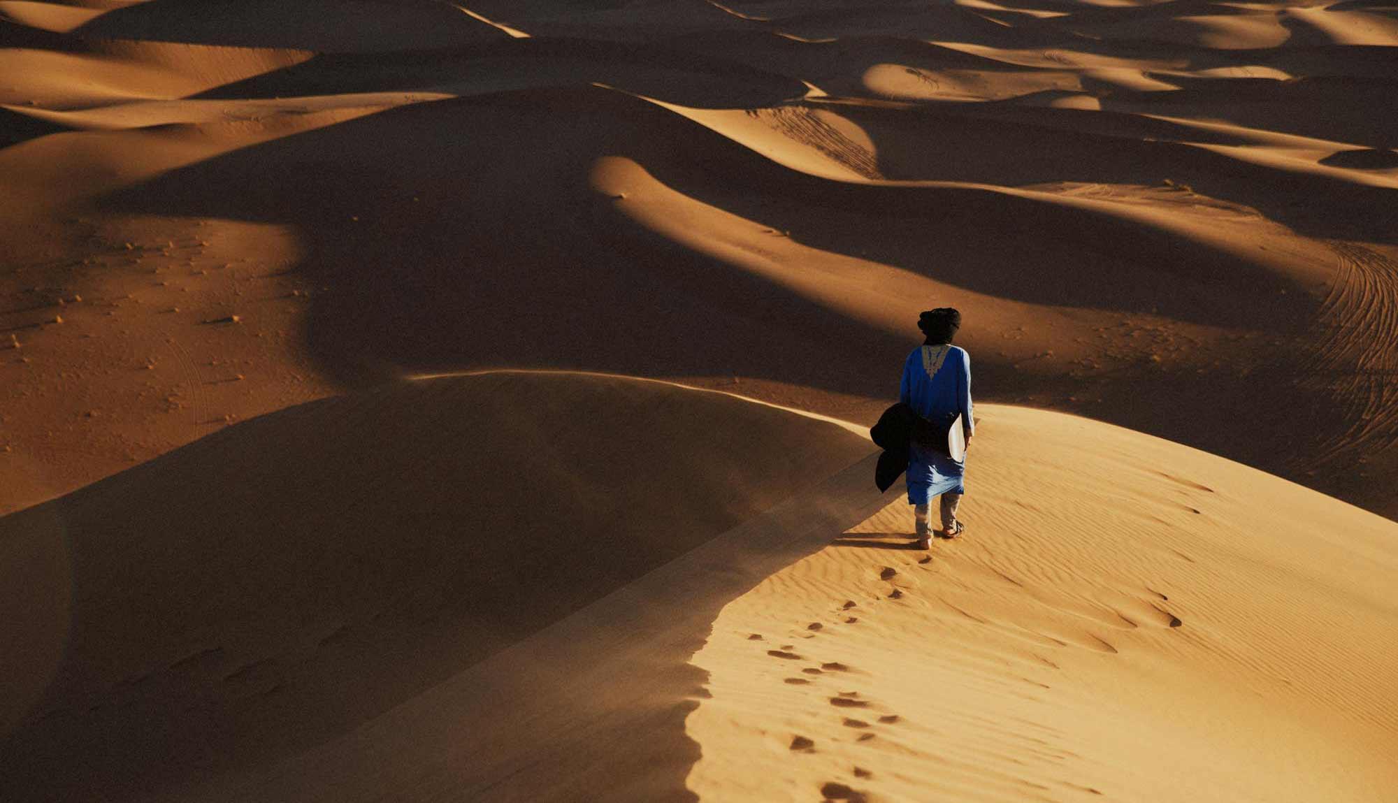 Beldi Nomad Walking Across Moroccan Desert Sand Dunes