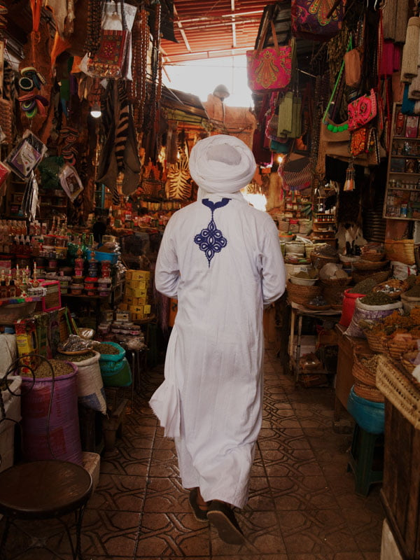 Man wearing traditional Berber clothes walking through the Souks of Marrakech